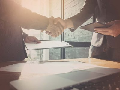 Businessman and partner shaking hands in office with vintage filter